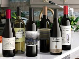 Six bottles of wine on a kitchen counter